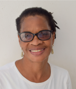 The image is of Veronica, the General Assistant and Driver. In the picture Veronica has medium length braids in a ponytail and she is wearing dark rimmed glasses. She is wearing a white t-shirt and the background is a white wall.